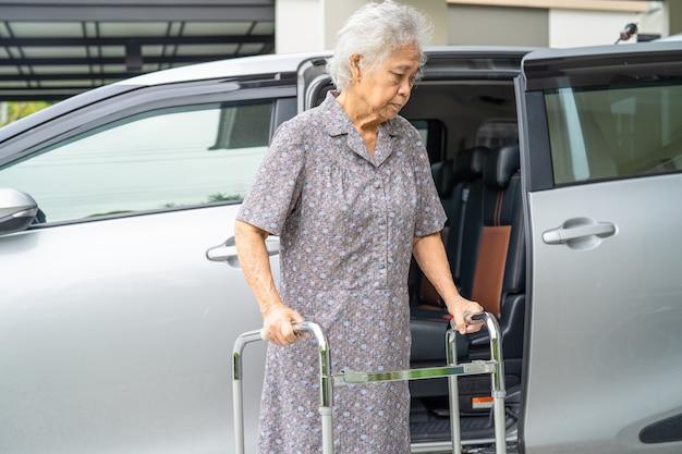 Азиатская старшая женщина-пациент гуляет с ходунками, готовится добраться до своей машины здоровой сильной медицинской концепцией