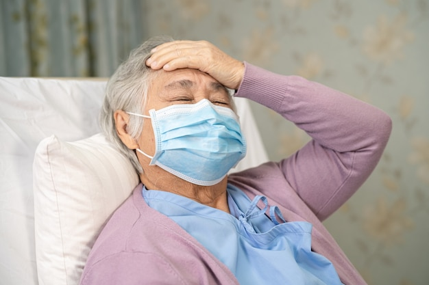 Asian senior woman patient wearing a face mask and headache for protect covid-19 coronavirus.