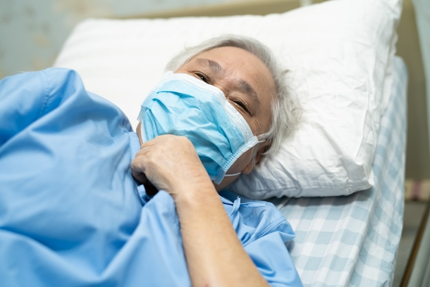 Asian senior woman patient wearing a face mask in hospital for protect coronavirus covid-19 virus.