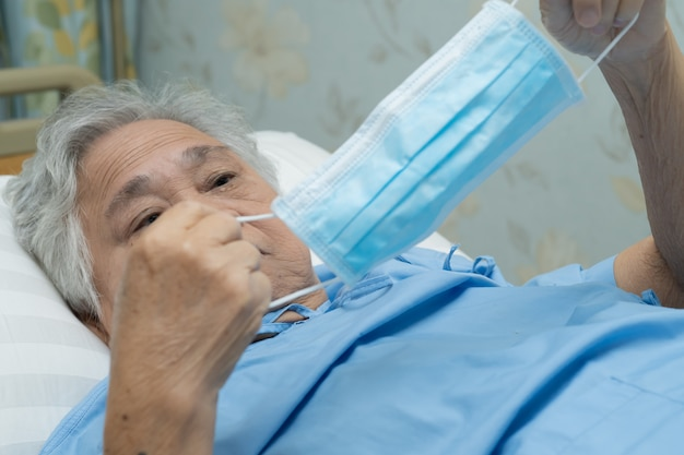 Asian senior woman patient wearing a face mask in hospital for protect covid-19 virus.