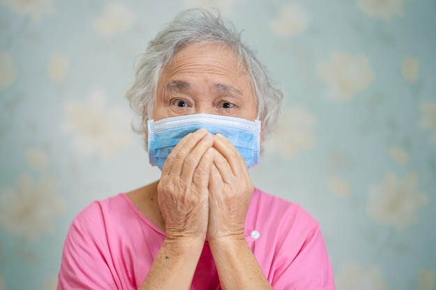 Asian senior woman patient wearing a face mask for protect covid-19 coronavirus.