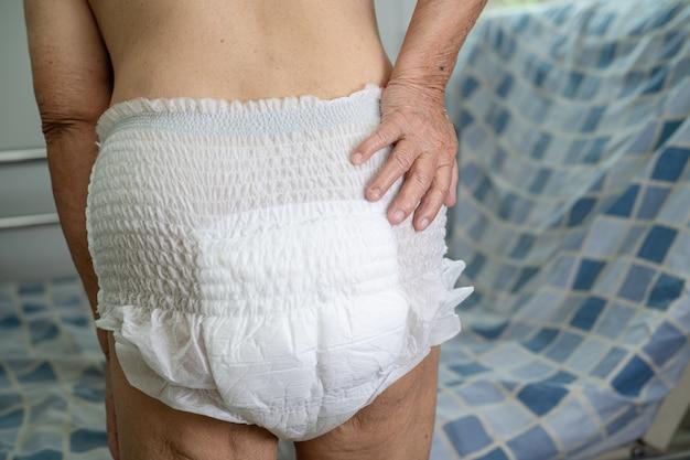 看護病院で失禁おむつを身に着けているアジアの年配の女性患者