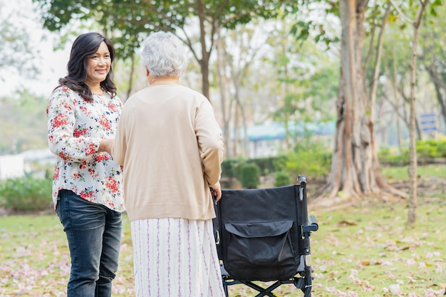 Asian senior woman patient on wheelchair in park
