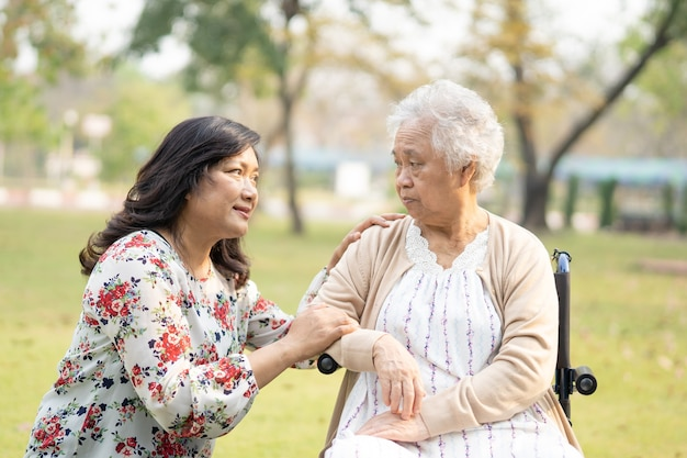 Asian senior woman patient with care help and support on wheelchair in park