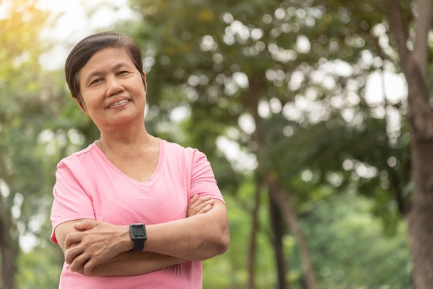 Asian senior woman in pink shirt smiling with arms crossed before exercising.