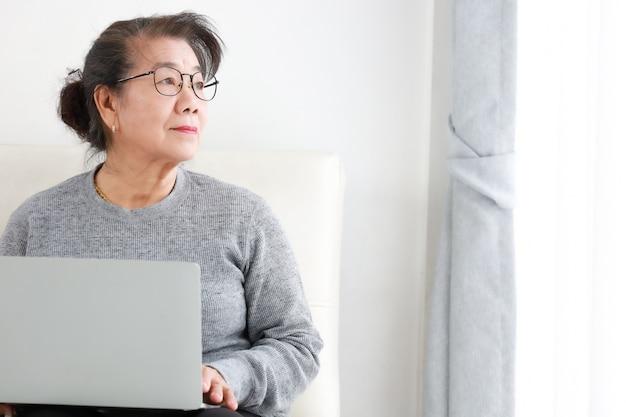 Азиатская старшая женщина на пенсию, используя портативный компьютер в гостиной