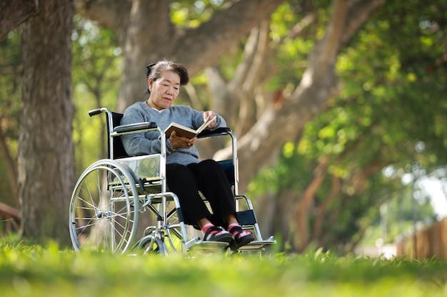 Азиатская старшая женщина сидя на кресло-коляске и читая книгу в улыбке сада сада и счастливом лице