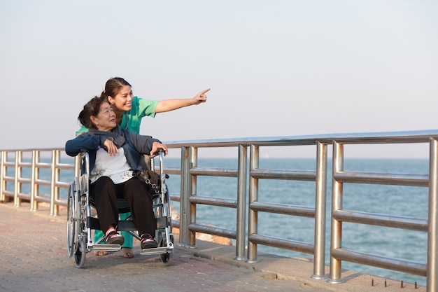 공원 병원에서 의사 유니폼 여자와 휠체어에 앉아 아시아 수석 여자