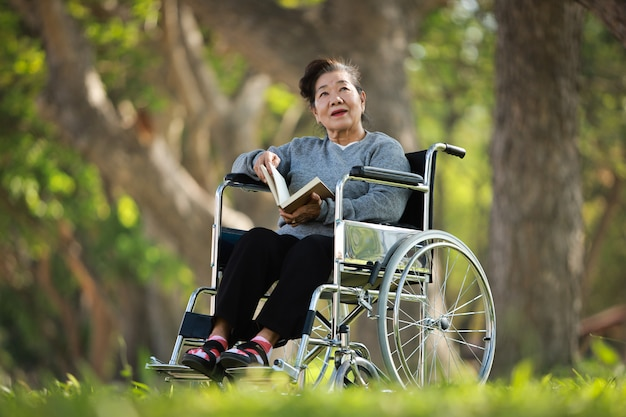 Asian senior woman sitting on the wheelchair and reading book in the park garden smile and happy face