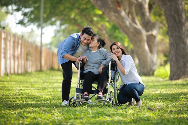 Asian senior woman sitting on the wheelchair with family happy smile face on the green park
