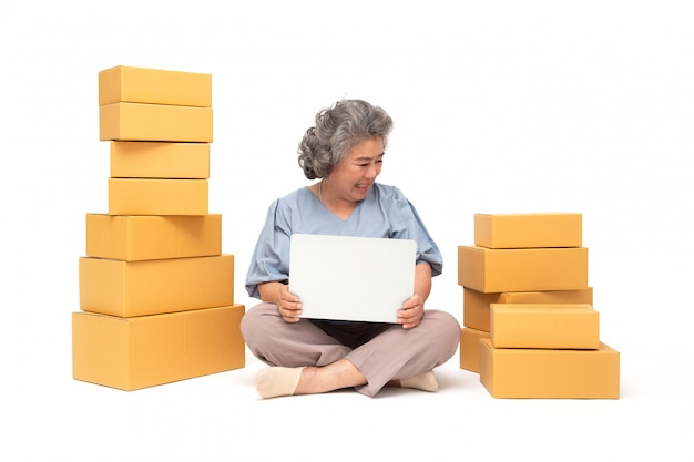 Asian senior woman startup small business freelance with parcel box and computer laptop and sitting on floor isolated on white wall, online marketing packing box delivery concept