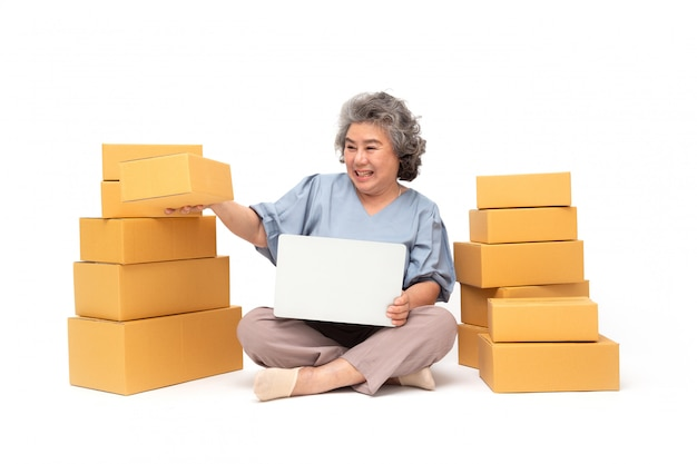 Asian senior woman startup small business freelance with parcel box and computer.