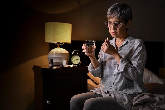 ベッドルームで薬を服用しているアジアの年配の女性