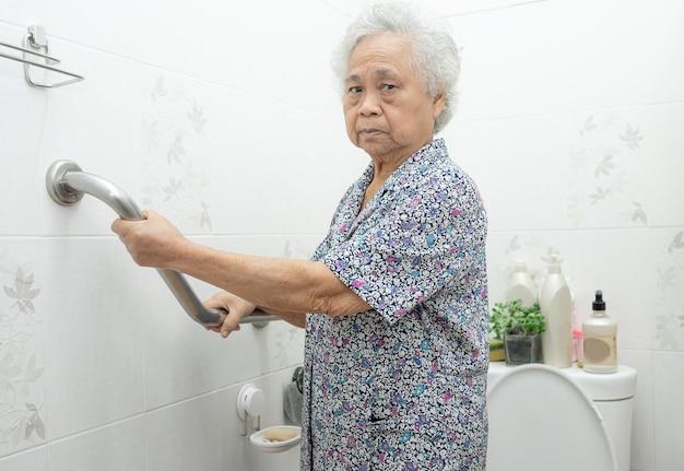 アジアの年配の女性はトイレのバスルームハンドルのセキュリティを使用しています。