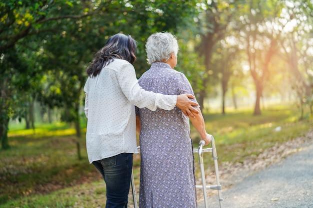 アジアの年配の女性は公園で散歩を使用します。
