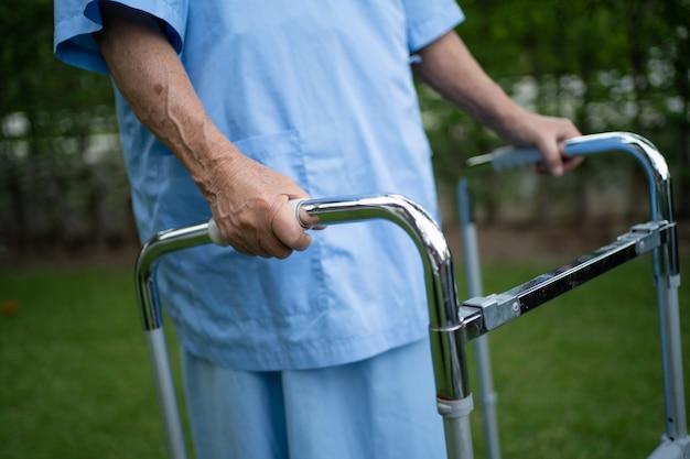 아시아 노인 여성은 공원에서 걷는 동안 건강이 좋은 워커를 사용합니다.