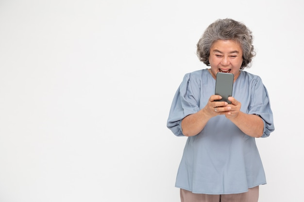 Asian senior woman using smartphone and receiving good news from the message on mobile chat application over white wall