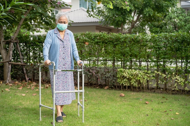 アジアの年配の女性は、コロナウイルスcovid-19を保護するために、歩行器とフェイスマスクを着用して歩きます。
