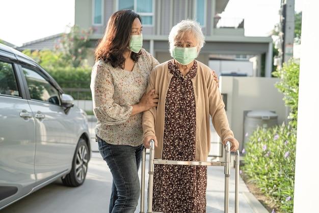 アジアの年配の女性は歩行器とコロナウイルスを保護するためのフェイスマスクを身に着けて歩く