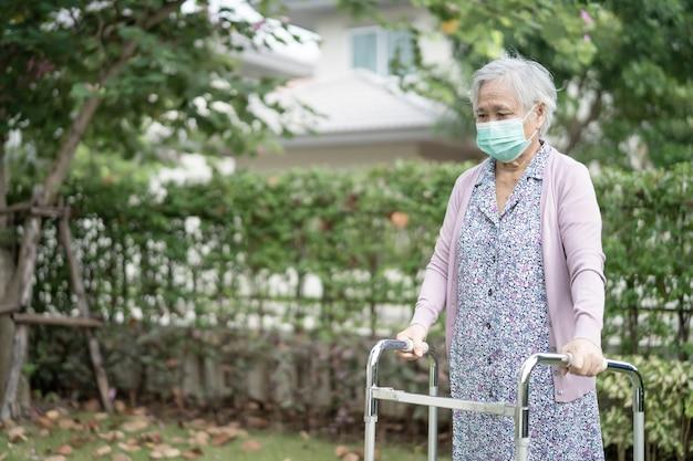 アジアの年配の女性は歩行器とコビッドコロナウイルスを保護するためのフェイスマスクを身に着けて歩く