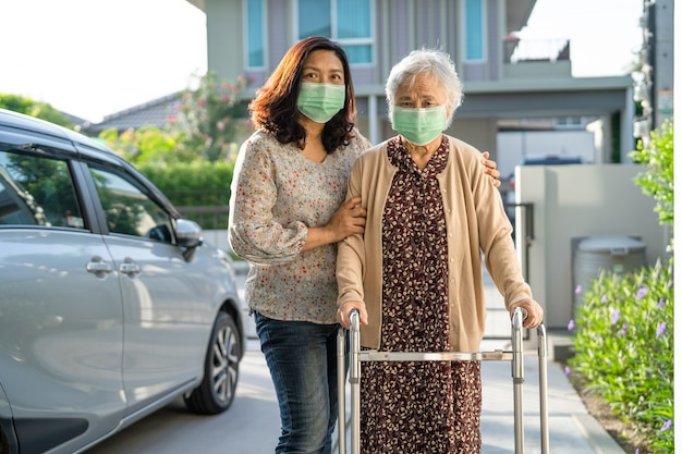 アジアの年配の女性は、コロナウイルスを保護するために歩行器とマスクを着用して歩く