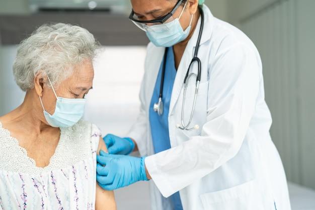 Asian senior woman wearing face mask getting covid19 or coronavirus vaccine
