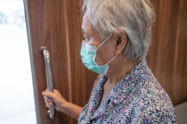얼굴 마스크를 쓰고 아시아 수석 여자 화장실 손잡이를 사용합니다.
