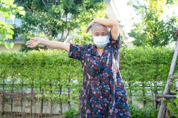 マスクを持つアジアの年配の女性は公園で幸せでコロナウイルスの運動を保護します