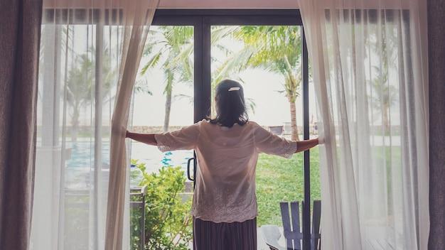 アジアの年配の女性がホテルの部屋に滞在しています