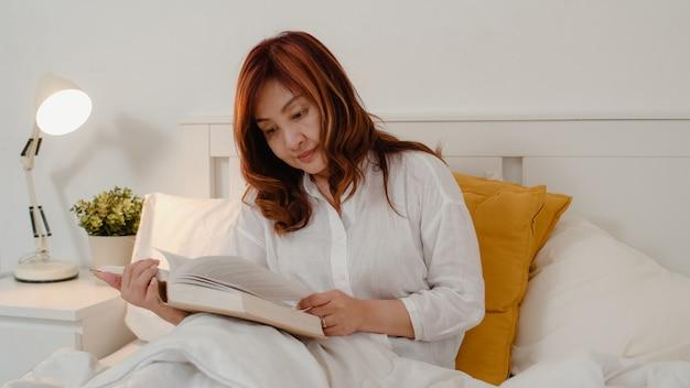 アジアの年配の女性は家でくつろいでいます。アジアのシニア中国女性は夜のコンセプトで自宅の寝室のベッドに横たわっている間本を読んで休憩時間をお楽しみください。