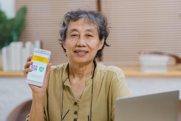 Азиатские пожилые женщины, сидящие в гостиной, держат дома и показывают экран мобильного телефона паспорта вакцины иммунитета covid-19. новая обычная виза здоровья для путешествий