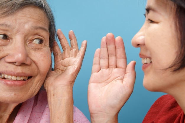 Asian seniors woman hearing loss , hard of hearing try to talk with daughter.