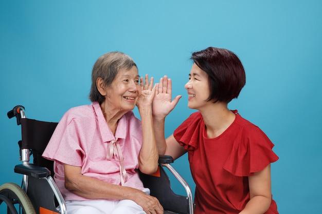 アジアの高齢者の女性の難聴、難聴は娘と話そうとします。