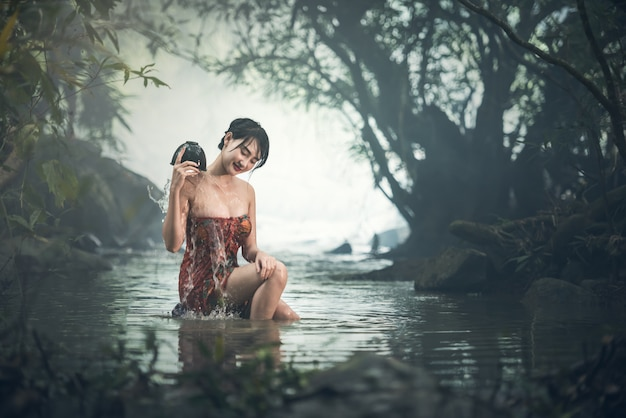 Asian sexy woman bathing in creek, thailand