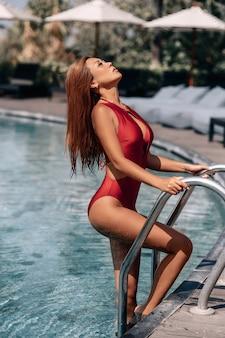 Asian sexy woman in burgundy bikini at swimming pool on a sunny day