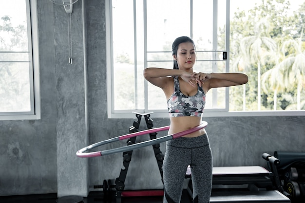 Asian sexy women are exercising with cardio by playing hula hoop in the gym. concept of health care with exercise in gym. beautiful girl playing fitness in the gym.