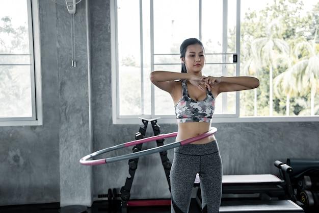 아시아 섹시한 여성은 체육관에서 훌라 후프를 연주하여 심장 운동을하고 있습니다. 체육관에서 운동과 건강 관리의 개념입니다. 체육관에서 피트 니스를 재생하는 아름 다운 소녀.
