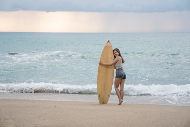 A asian sexy young woman walking on beach with surfboard at phuket thailand