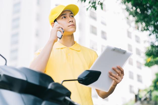 アジアの荷送人が商品を入手するために顧客に電話をかけています