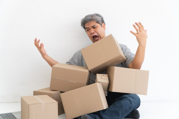 Asian shopaholic man shocked and sitting on the floor in the living room