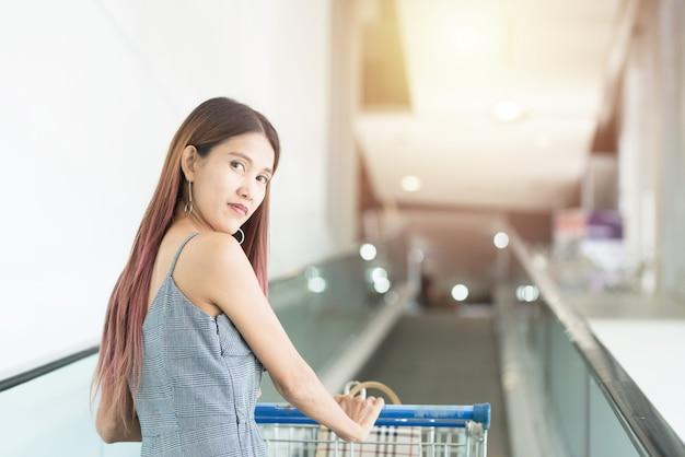 Азиатская женщина покупателя с магазинной тележкой на движущейся дорожке до второго этажа торгового центра.