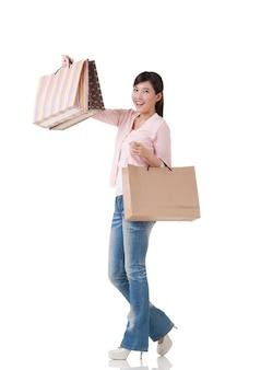 バッグを保持しているアジアのショッピング女性、スタジオの白い背景に反射と全身の肖像画。