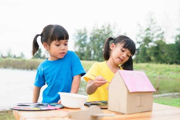 종이 집에 그림을 그리고 색칠하는 아시아 형제 아이들