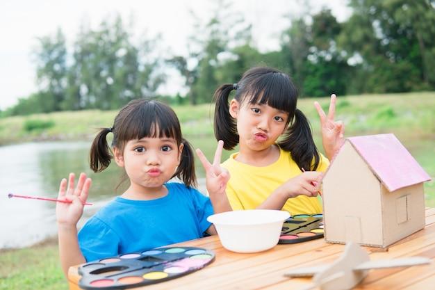 종이에 그림을 그리고 색칠하는 아시아 형제 아이들