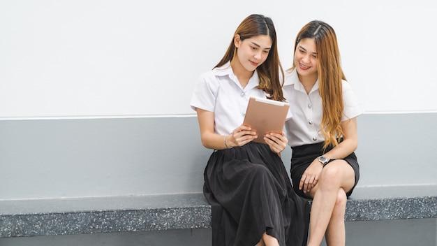 Азиатские братья и сестры студентов колледжа в студенческой форме общаются и смотрят на цифровой планшет, чтобы вместе учиться в университетском городке. сток фото