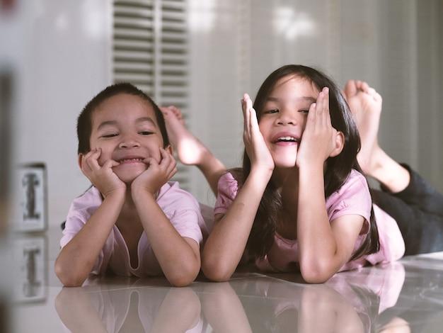 Covid-19 대유행 기간 동안 아시아 형제 학교 아이들 소년과 소녀가 차가워졌습니다. 아이들은 집에서 잠겨 있거나 자기 격리되어 있습니다. 가족 지원의 개념.