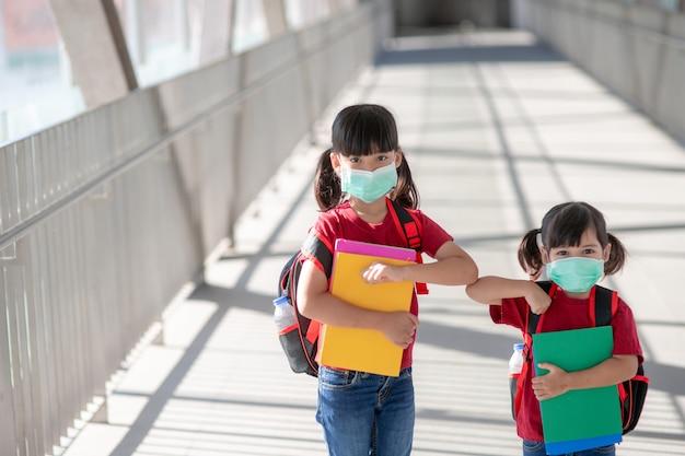 코비드-19 검역 및 폐쇄 후 학교에 돌아가는 얼굴 마스크를 쓴 아시아 형제