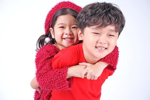 白で隔離のクリスマスの衣装と赤いセーターのアジアの兄弟