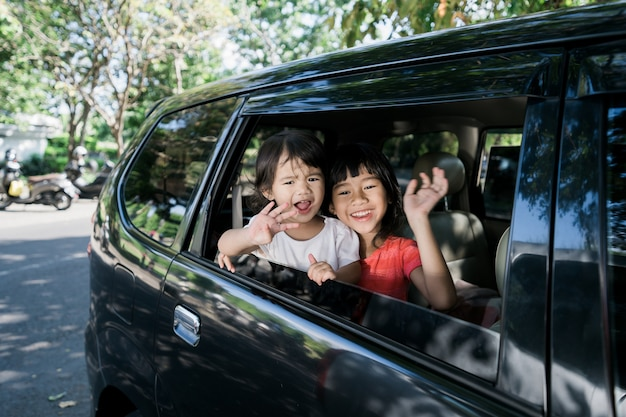 Asian siblings waving hands from window and travel by car