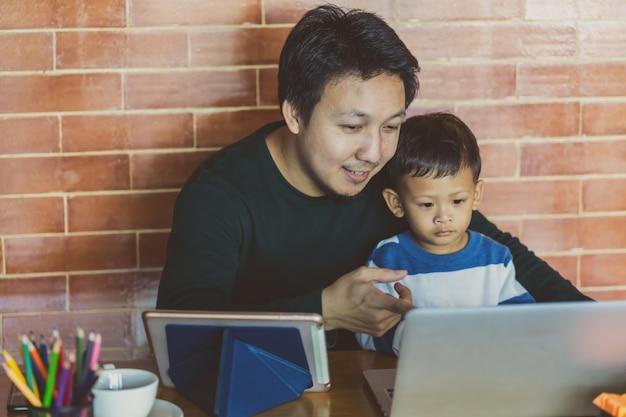 Asian single dad with son are looking the cartoon via technology laptop together